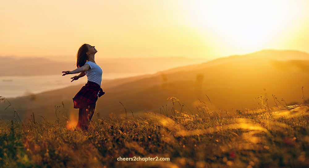 Image of woman opening arms on mountain top feeling joy - main image for cheers 2 chapter 2 unmet expectations in life page