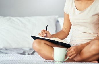 woman writing in a journal while in bed drinking coffee as part of her morning routine