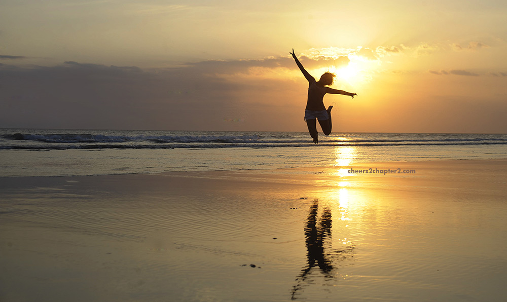 image of woman jumping for joy on beach at sunset