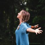 Smiling woman in forest with arms outstretched for how to get negative thoughts out of your mind blog page
