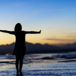 woman standing by ocean deciding to take a risk and feel fierce