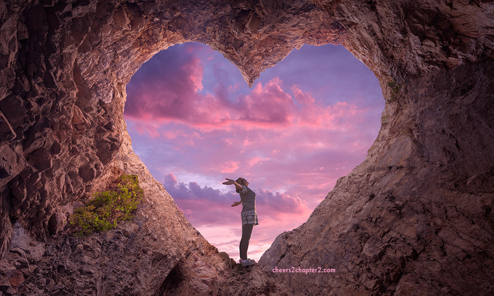 letting go of self-consciousness Image of woman standing in a rock heart looking like she is feeling happy and free