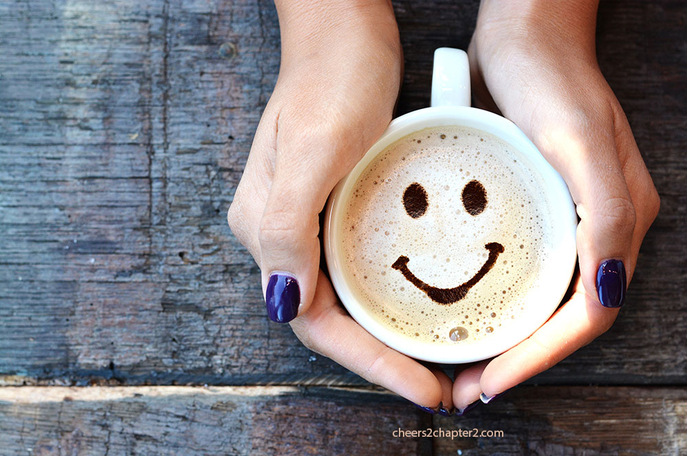 Image of woman's hands holding a cup of coffee with smile in it