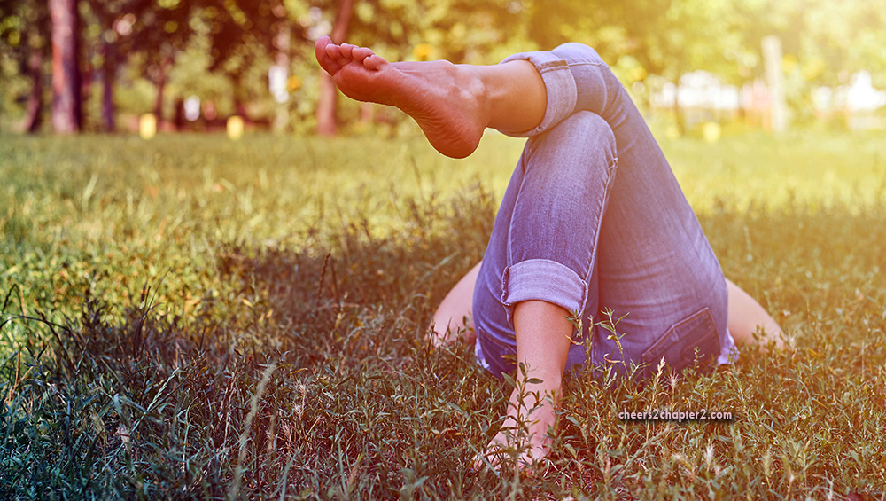 Woman lying in the grass barefoot for How to Get Yourself Grounded and How It Can Help You