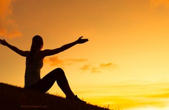 Woman on HIll with outstretched arms toward sun light for how do you know your purpose page