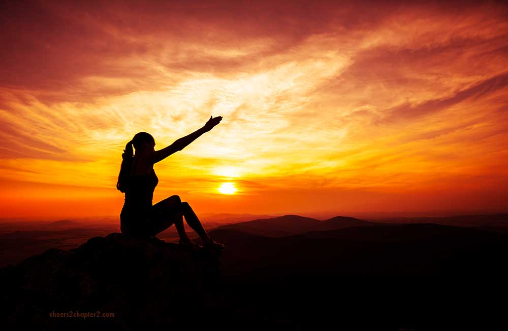 Woman on top of hill reaching arms up for How Do you Overcome Setbacks page